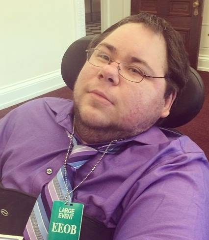 Dominick at the White House for a forum on LGBT and disability issues wearing a purple button down shirt, a purple and light blue striped tie, and a green Live Event badge, sitting in his black wheelchair.