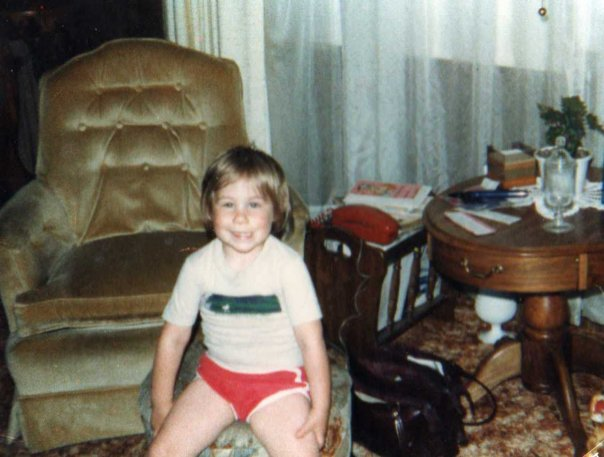 Dominick in his brother's hand-me-down clothing, with a big smile on his face, sitting on a piece of furniture in front of a chair in a retro looking 1980s looking home