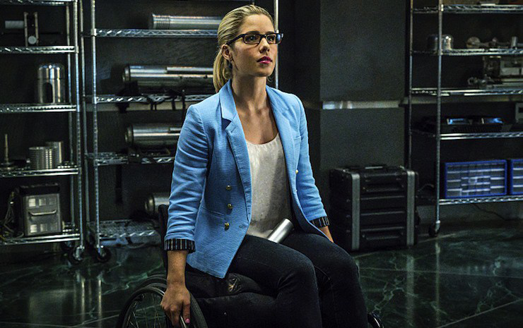 Emily Bett Rickards as Felicity Smoak sits in a manual wheelchair with her hands on the wheels. She is wearing a white shirt under an open blue shirt/jacket, and glasses and seems to be in a room with tech gear behind her