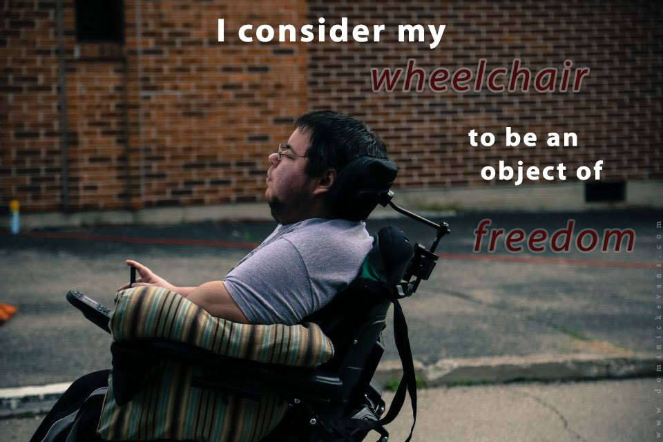 Dominick sits in his wheelchair on an outdoor film set, a red brick wall behind him. He is looking outward to the left, wearing a gray t-shirt, with a pillow propped under his arm. The image has the words I consider my wheelchair to be an object of freedom.