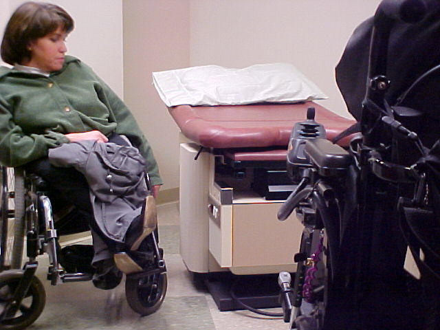 a woman in a wheelchair sits next to a small, empty examination table in a doctors office. It is a pink table with white paper crumpled on it. Another wheelchair user is sitting in the foreground on the right