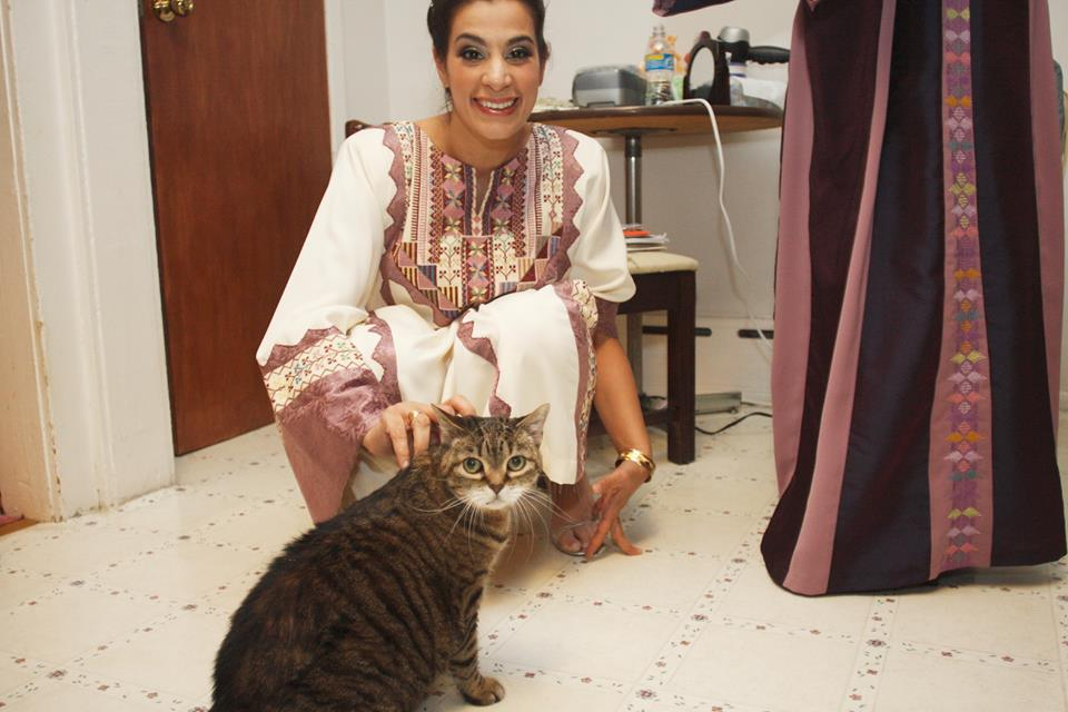 Maysoon is kneeling down, smiling at the camera, as she puts her hand on her cat Lucy.