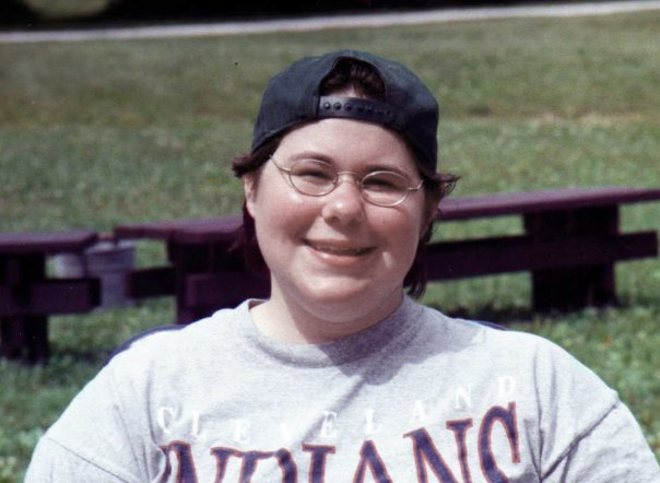 Dominick, as a teenager. A smiling face, wearing glasses, a background baseball cap, and a t-shirt, is visible from the shoulders up. There are picnic benches and grass in the background and only a little part of his wheelchair seat back is visible.