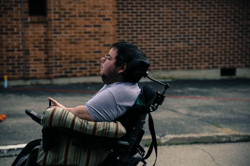 Dominick, a dark haired person of European descent looks facing forward, the camera shooting him straight on facing his left side. He is sitting in his wheelchair on his film set, watching something seen off camera, deep in thought. There is a red brick wall behind him in the distance.