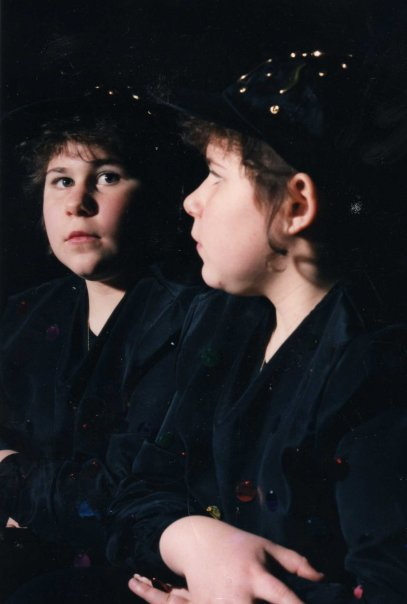 Dominick, a Caucasian, Polish American, at age 13. He has a contemplative expression on his face. There is a curl wisp near his ear, and he wears a black silk shirt and black ball cap. His hair is dark brown and braided beneath the cap. He is looking in a mirror, and his reflection is visible.