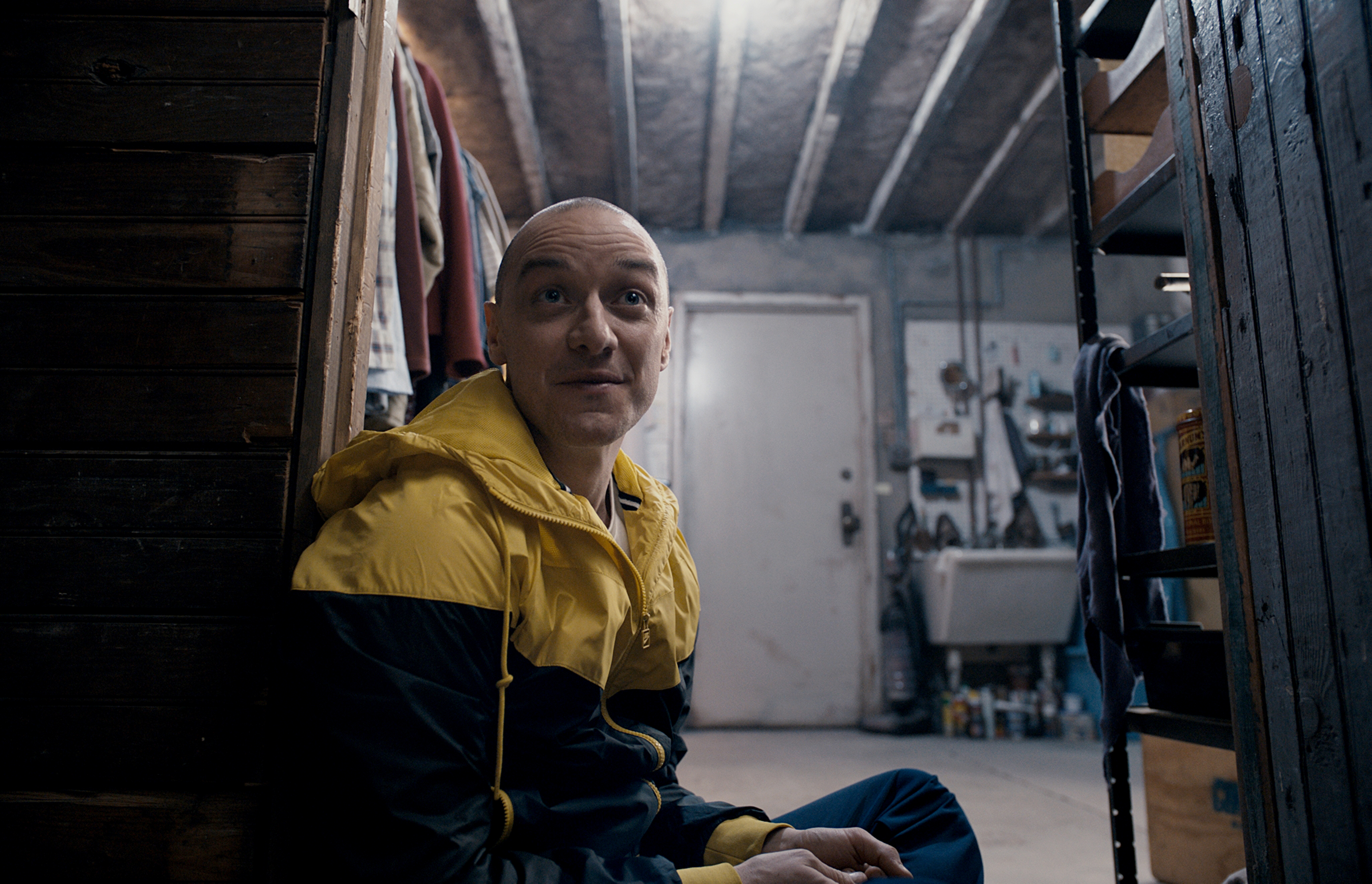 A screenshot of James McAvoy, in Split. He is sitting on the left side of the screen, staring into the camera with a creepy expression on his face. His head is nearly bald, with some shaved black stubble on the back of his head. He wears a yellow and black winter jacket. He is in some old garage or shed or basement, with a doorway in the background and a shelf with stuff on it, like paint cans, is visible in the right foreground.