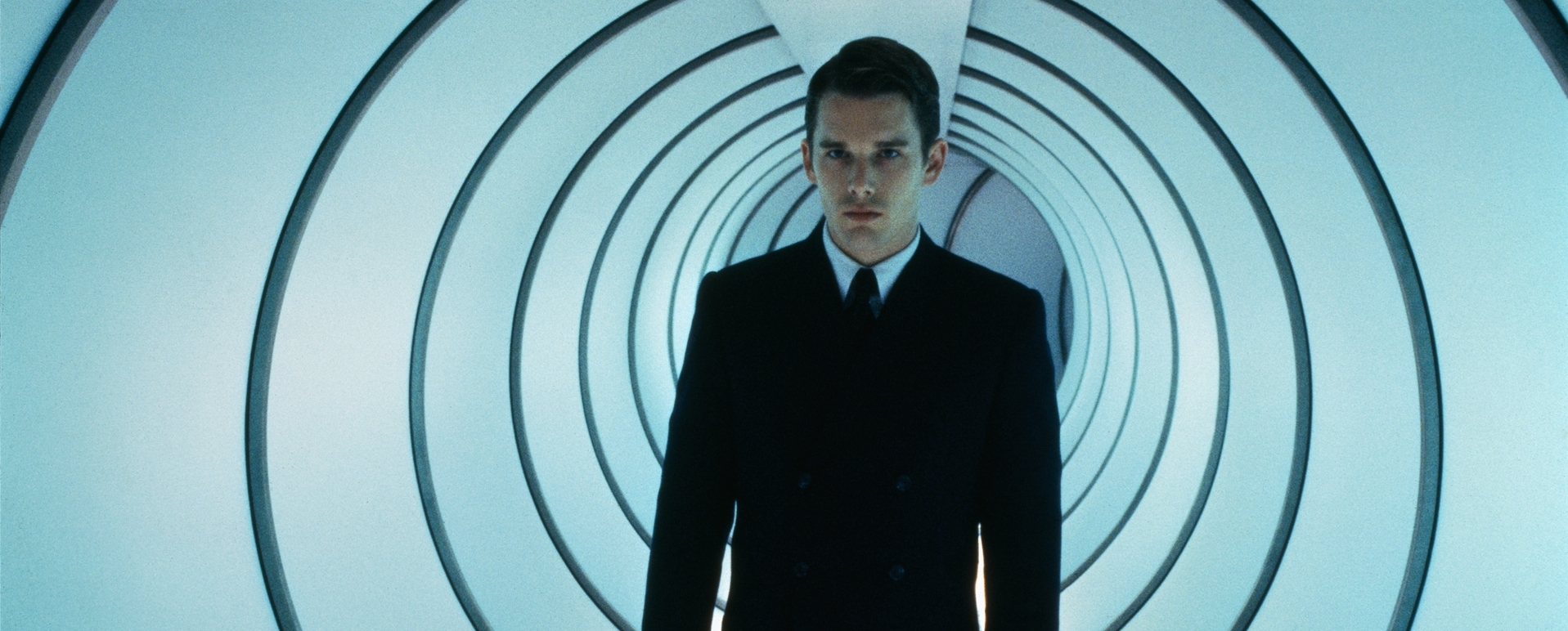 A photo of Ethan Hawke as Vincent pretending to be Jerome. He is wearing a suit, and is standing in a tunnel that appears to be bluish white in color. The tunnel is circular, and has black lines running around the circle in between from space to space behind him.