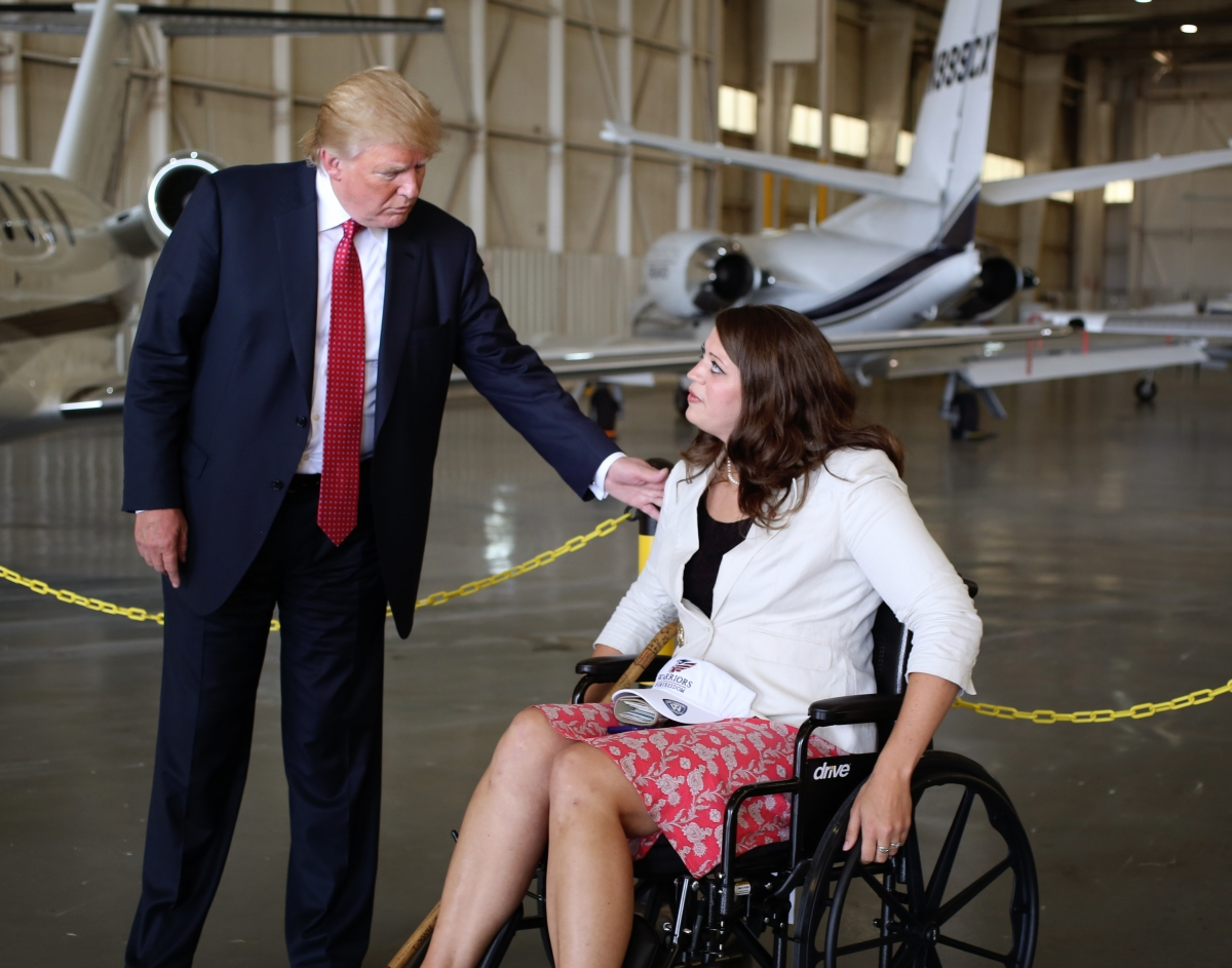 Donald Trump stands looking down at a woman in a wheelchair, who is looking up at him with a bewildered expression on her face. He has his hand mirror her shoulder, as he stands over her. There appears to be the tail end of an airplane in the background.