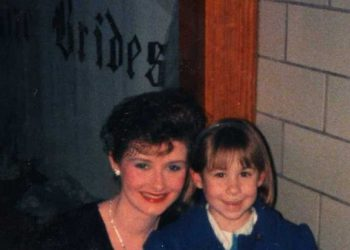 Dominick as a young child. He has dark blonde hair down to his shoulders with bangs. He wears a headband and is wearing a nice blue jacket with gold buttons. He is standing next to one of his former camp counselors at her school play. She is leaning down next to him, holding papers and a book. She is in stage makeup, wearing a black dress and has black gloves on. This is taken at Anthony Wayne high school in the 1980s.